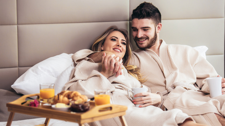 happy couple in robes eating in bed