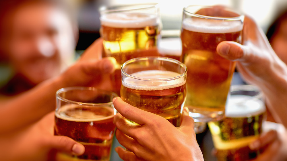 Five hands holding full beer glasses