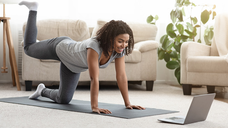 woman exercising to fitness video on laptop
